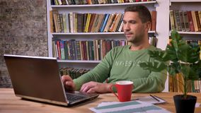 Office worker types on the laptop and moves to the pace of music. Bookshelvers on the background stock video