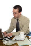 Office Worker Typing. A young office worker wearing glasses is typing on his laptop computer, isolated against a white background Stock Photo