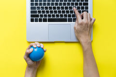 Office worker typing email on computer. Feels stressed and nervous, holds a stress ball in her hand Royalty Free Stock Photography