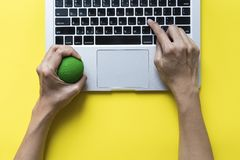 Office worker typing email on computer. Feels stressed and nervous, holds a stress ball in her hand Stock Images