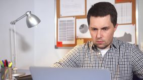 Office worker typing at notebook and thinking. Serious man at work in the office. Office worker typing at notebook and thinking stock video footage