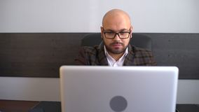 Office worker typing report on computer. Businessman working on laptop computer in the office. 4 k bearded man stock video footage
