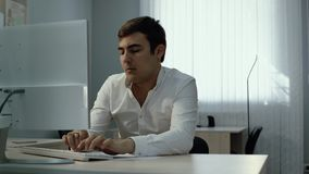 Office worker typing on wireless keyboard and writes with pen in notebook. Office man worker typing on wireless keyboard and writes with pen in notebook in stock footage