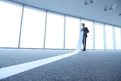 Office worker unrolling long sheet Royalty Free Stock Photography