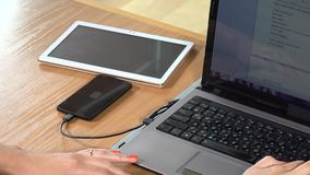 Office worker using computer and wired smart phone charging on table. closeup. Female office worker using laptop computer and wired smart phone charging on table stock footage