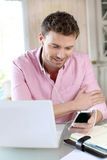 Office worker using laptop and phone Royalty Free Stock Image