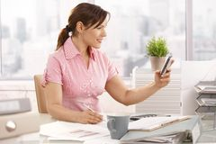 Office worker using mobile phone. Casual office worker sitting at office using mobile phone, smiling stock photos