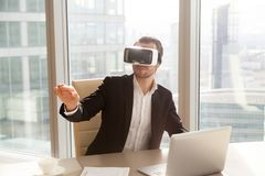 Office worker in vr headset pointing in the air. Businessman in VR headset glasses pointing finger in air. Office worker or CEO immersed in virtual reality Stock Images