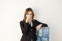 Office Worker at Water Cooler. Female office worker getting a drink at water cooler. Horizontally framed shot Stock Image