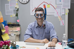 Office worker wearing scuba mask. Smiling office worker wearing scuba mask with negative business chart on background Royalty Free Stock Images
