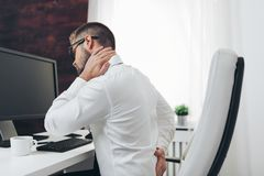 Free Office Worker With Pain From Sitting At Desk All Day Stock Photos - 150703843