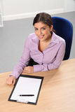 Office worker woman at desk with pen and paper Royalty Free Stock Image