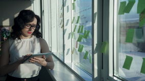 Office worker woman looking to tablet, stickers pasted on window stock video footage