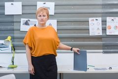 Office worker woman stands near a table with a folder in her hand. Inside the office. stock photos