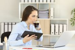 Office worker working and drinking coffee. Looking away Royalty Free Stock Photo