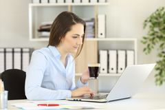 Office worker working online holding a coffee cup Stock Photo