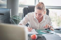 Office worker at workplace. Girl writing on paper. Workplace stock images