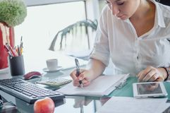 Office worker at workplace. Girl writing on paper. stock photography