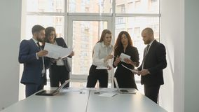 Office workers, the company`s young team, two men and three women discuss the installation documents for the company. Standing near the table 4k stock footage