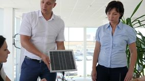 Office workers discuss development and possibilities solar panels in modern office stock video footage