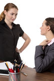 Office workers discussing in the office. Two female co-workers in an office.  One sitting at a desk wearing a suit and another standing opposite, having a Royalty Free Stock Photos