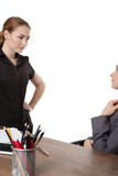 Office workers discussing in the office. Two female co-workers in an office.  One sitting at a desk wearing a suit and another standing opposite, having a Royalty Free Stock Photo