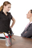 Office workers discussing in the office. Two female co-workers in an office.  One sitting at a desk wearing a suit and another standing opposite, having a Royalty Free Stock Photography