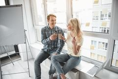 Office workers drinking hot beverage. Happy guy and girl enjoying coffee break together. They are sitting in workroom and clinking with paper cups Royalty Free Stock Image
