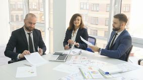 Office workers, employees of a large company, two young men, company executives and a woman are sitting at the table. Signing documents 4k stock footage