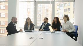 Office workers, employees of a large company, two young men and three young women sitting at a table discussing all the. Company`s questions, the end of the stock video footage