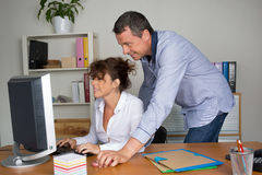 Office workers in front of computer in a bright office Royalty Free Stock Photography