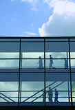 Office workers in glazed walkway. Office workers walking through glazed walkway as silhouettes, blue sky and modern architecture Royalty Free Stock Photography