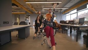 Office workers have fun in the office and rolling in office chairs