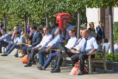 Office workers having a lunch in park next to st. Paul cathedral. London, UK. LONDON, UK - SEPTEMBER 10, 2015: Office workers having a lunch in park next to st stock photography