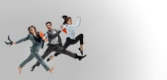 Office workers jumping isolated on studio background stock photo