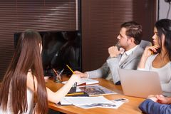 The office workers, in the office are looking at something on a black monitor. Indoors. royalty free stock photography