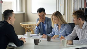 Office workers meet during coffee break to discuss working details. Blonde woman in blue blouse, who sits in middle, asks questons to man in black shirt, that stock footage