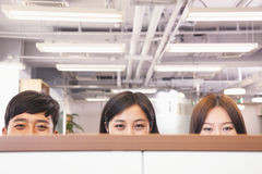 Office workers peeking over divider in office Royalty Free Stock Photo