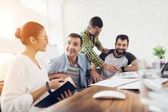 Office workers and a person in a wheelchair discuss working matters. They work in a bright office. Office workers and a person in a wheelchair discuss working Royalty Free Stock Image