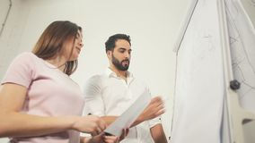 Office Workers Prerape for Training. Two intelligent and lovely office workers preparing for the training, solving maths tasks while writing on the whiteboard stock footage