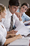 Office workers reviewing reports Stock Image