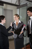 Office workers shaking hands at door of boardroom Stock Photo