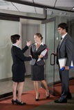 Office workers shaking hands at door of boardroom royalty free stock photography