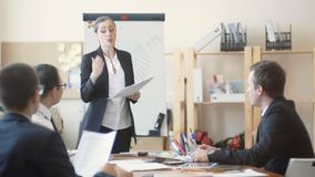 Office workers sit quietly and listen to remarks from the woman boss stock footage