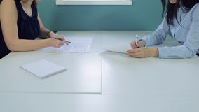 Office workers sitting opposite each other working with documents stock video
