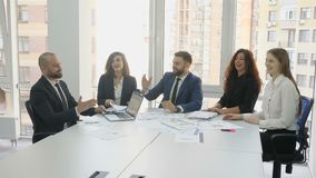 Office workers sitting at a square table discussing all the issues of the contract, two men shake each other`s hands. And three female employees clap their stock footage