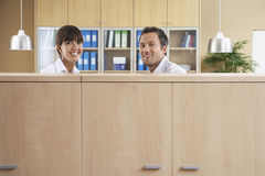 Office Workers Smiling Behind Cubicle Royalty Free Stock Photography