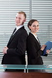Office workers standing back to back Royalty Free Stock Photos