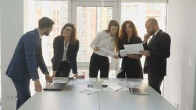 Office workers standing at a square table discuss financial issues of the firm, a young team of three women and two men. Prepare a report on all matters of the stock video
