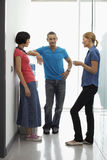 Office Workers Talking By Water Cooler In Hallway Royalty Free Stock Photo